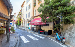 Street view in Antibes old town, France. Antibes, France - June 29, 2016: day view of typical street with bistrot in Antibes, France. Antibes is a popular Stock Photos