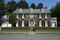 Street view of a brick colonial house in an affluent neighborhood stock photo