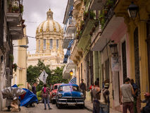 Street with view on capitol in Havana, Cuba. Havana, Cuba on January 14, 2016: Cuban people and oldtimer on street with view on capitol in La Habana Royalty Free Stock Photo