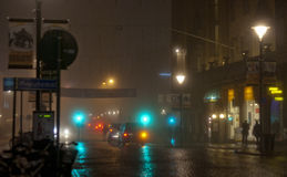 Street view in the city on a foggy night. A thick fog over the city at night, with lot of mood and shadows and a colorfull glow from the trafic lights and the royalty free stock image
