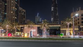 Street view of Dubai skyline timelapse and rush hour traffic in downtown at night. Road with palms and modern towers on background stock footage