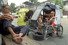 Street view with Filipino bike mechanic and children. Philippines, Luzon island capital city Manila while the bicycle repairman as equipping of his work, his Royalty Free Stock Photos