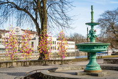 Street view of inactive fountain with traditional colourful feathers on trees for Easter decorations in Uppsala, Sweden, Europe Royalty Free Stock Photo