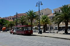 Street view of La Maddalena`s city with sightseeing train Royalty Free Stock Photography