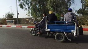 Street view of local people driving on three wheeler pickup. ASWAN, EGYPT - FEBRUARY 6, 2016: Street view of local people driving on three wheeler pickup stock video