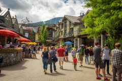 Street view with many tourists  in Whistler Village. WHISTLER, BRITISH COLUMBIA, CANADA - JULY 2, 2017 : Scenic street view with many tourists  in Whistler Stock Photo