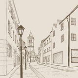 Street view in old european city. Retro cityscape - houses, buildings, tree on alleyway. Royalty Free Stock Photography