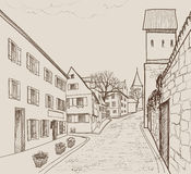 Street view in old european city. Retro cityscape - houses, buildings, tree on alleyway. Royalty Free Stock Images