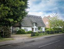 Thatched Cottage in an English Village. Street view of an old thatched cottage in the pretty village of Foxton, Cambridgeshire, England, UK Stock Photos