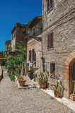 Street view with pebble walkway, flowering plants and blue sunny sky at Colle di Val d`Elsa. Street view with pebble walkway, flowering plants and blue sunny Royalty Free Stock Photo
