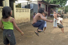 Street view with playing Nicaraguan children. Nicaragua, capital, city Managua: in the deprived area, slum Jorge Dimitrov, boys and girls jumping rope on the stock images