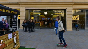 Street View in a Shopping Area. BATH, UK - OCTOBER 20, 2015: People pass an Apple store in the city centre. The American multinational tech giant operates 463 Royalty Free Stock Photography