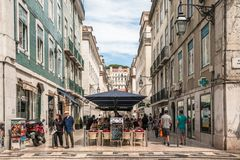 Street view of shops and cafes in traditional old buildings. Lisbon, Portugal - August 23, 2017 Cafe and restaurant in busy historic center Baixa District Royalty Free Stock Photos