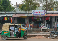 Street view with small shops and motor rickshaw. Royalty Free Stock Images