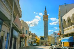 Street view with tall minaret in old town Nabeul. Tunisia, Nort. Cityscape with tall minaret tower of mosque in Nabeul. Tunisia, North Africa Stock Images