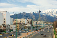 Street View of Tehran with Milad Tower and Alborz Mountains Royalty Free Stock Image