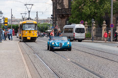 Street view with yellow train, sport car and tourists Royalty Free Stock Photo