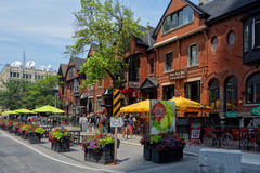 Street views of the historic Toronto. A historic red brick building on the first floor of which there are restaurants with  tables under yellow umbrellas Royalty Free Stock Photography
