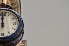 Street vintage clock on an old building on gray sky background. Part or a Half of the dial of retro watches royalty free stock photography