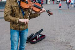 Street violinist plays the violin at noon stock images