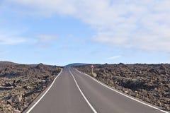 Street through volcanic area in Timanfaya national park Stock Photo