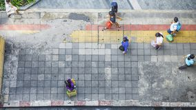 On street walk in top view man and woman with shopping bags. Stand on square block pedestrian walk way with yellow and red line for guide blind people walk Royalty Free Stock Images