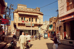 Street with walking people and historical houses with fresco and carvings, Rajasthan. Stock Photos