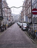 On the street walking people and moving vehicles. Amsterdam,the Netherlands-December 30,2016:On the street walking people and moving vehicles Royalty Free Stock Image