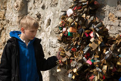 Street wall of colorful hanging padlocks with blonde boy Stock Image