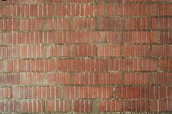 Street wall of red bricks embossed with the uneven walls royalty free stock images