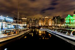 Dancing Houses and Boats at Damrak At Night in Amsterdam. The street was located on a rak reach, a straight part of the Amstel river near a dam.Former stock Royalty Free Stock Image
