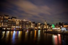 Dancing Houses and Boats at Damrak At Night in Amsterdam. The street was located on a rak reach, a straight part of the Amstel river near a dam.Former stock Stock Photos