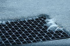 Street water storm drain with heavy flowing runoff Royalty Free Stock Image