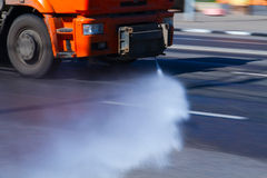 Street watering. Watering machine waters the asphalt street surface by a hot dry summer day to make it wet Stock Photos