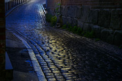 Street with wet cobblestones at night in an old town Stock Images