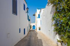 Street in white blue town Sidi Bou Said with blue flowers,Tunisia, North Africa royalty free stock photo