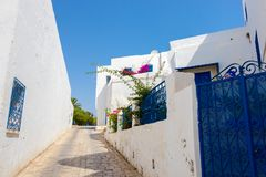 Street in white blue town Sidi Bou Said with magenta flowers, Tunisia, North Africa royalty free stock image