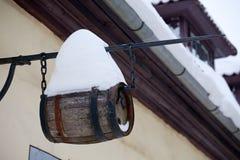 Street wine keg. Small wine keg with big snowdrift hanging on house wall Stock Photo