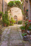 Street With Stone Arch Decorated With Plants (Spello) Stock Photography