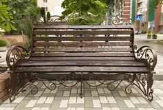 Street wooden bench is painted in bronze color. The street wooden bench is painted in bronze color with a metal frame and beautiful forged ornament and elements stock image