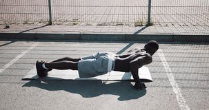 Street workout. Athletic African American man doing push-ups and spin exercise on outdoors. A black man is playing stock footage