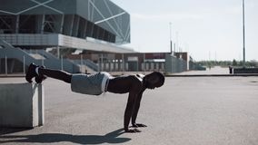 Street workout. Athletic African American man doing push-ups and spin exercise on outdoors. A black man is playing