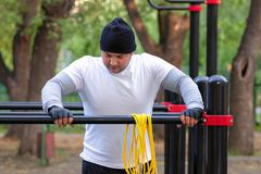 Street workout of a young man in the early Sunny morning. The man is preparing to perform a power load on the simulator and rubs stock photography