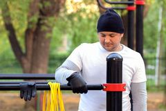 Street workout of a young man in the early sunny morning. The man is preparing to perform a power load on the simulator stock images