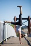 Street yoga: Adho Mukha Vrikshasana variation. Yoga in the city: beautiful sporty teenage girl working out on the old bridge on summer day, leaning on railing Stock Photography