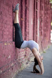 Street yoga: handstand. Yoga in the city: beautiful sporty young woman working out on the street beside old red brick wall, doing handstand, variation of Adho Royalty Free Stock Photo