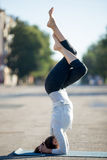 Street yoga: salamba sirshasana with Garudasana legs. Yoga in the city: beautiful young sporty woman working out on the street on summer day, doing Garuda Royalty Free Stock Photo