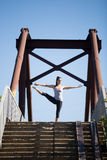 Street yoga: Utthita Hasta padangushthasana. Yoga in the city: beautiful young fit woman working out on the old bridge on summer day, doing Utthita Hasta Royalty Free Stock Images