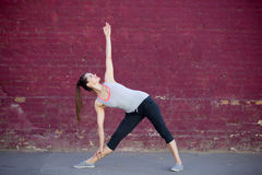 Street yoga: Utthita Trikonasana Pose. Yoga in the city: smiling beautiful sporty young woman working out on summer day on the street in front of old red brick Stock Image