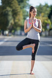 Street yoga: Vrksasana pose. Yoga in the city: smiling beautiful young sporty woman wearing sportswear working out on pedestrian crosswalk on empty road on the Stock Photo